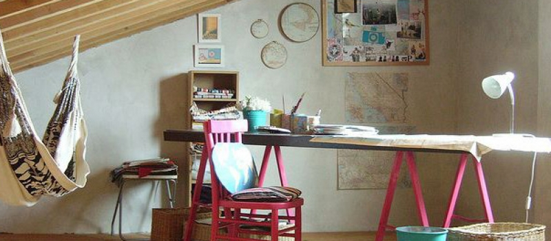 Hipster home office. Desk with pink legs and pink chair. Hammock in the corner.